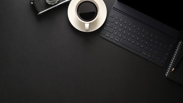 ワイヤレスキーボード、コピースペース、カメラ、コーヒーカップのある職場の黒いテーブルのトップビュー