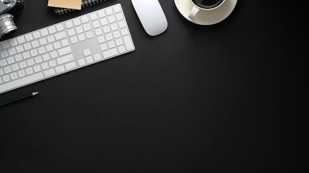 黒いテーブルの上のコンピューターのキーボード、コピースペース、コーヒーカップと職場のトップビュー