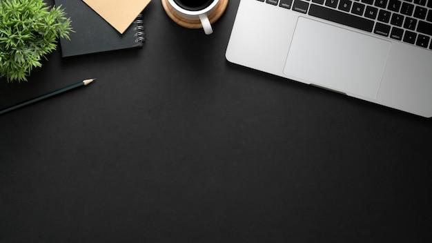 黒いテーブルの上のノートパソコン、コピースペース、文房具、コーヒーカップと職場のトップビュー