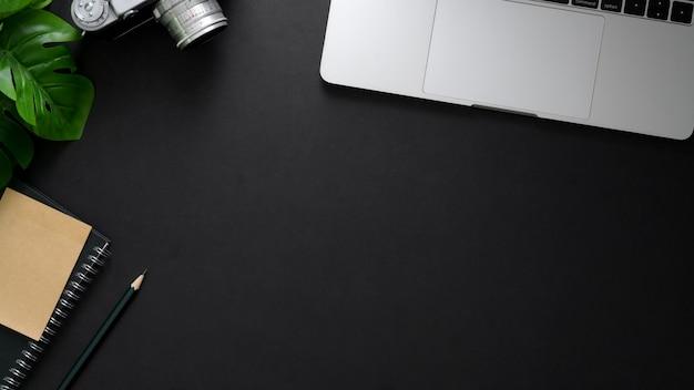 ノートパソコン、コピースペース、文房具、黒いテーブルの上のコーヒーカップと職場のオーバーヘッドショット