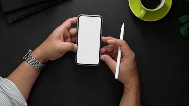 職場でリラックスしながらスマートフォンを使用して男性のフリーランサーのオーバーヘッドショット