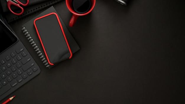 黒いテーブルにワイヤレスキーボード、スマートフォン、コピースペース、コーヒーカップのある職場のトップビュー
