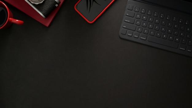 Вид сверху на рабочем месте с беспроводной клавиатурой, смартфоном, копией пространства и камерой на черном столе