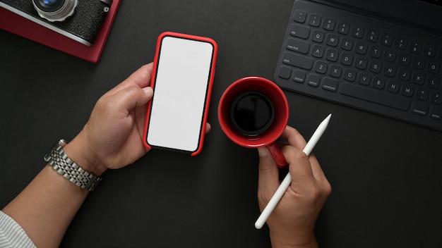 スタイリッシュな職場で作業しながらスマートフォンを保持している男性のカメラマンのオーバーヘッドショット