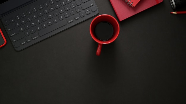 ワイヤレスキーボード、事務用品、コピースペース、黒いテーブルの上の赤いコーヒーカップとスタイリッシュな職場の平面図