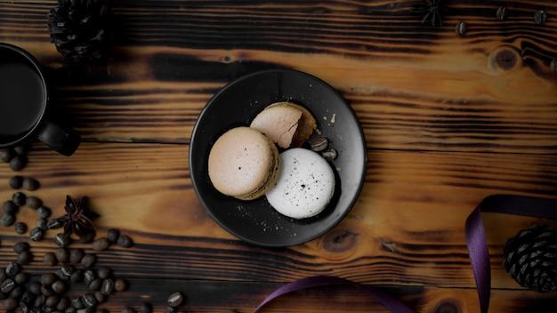 Вид сверху кофейных макарон на черной тарелке с фиолетовой лентой, кофейными зернами и сухими розами
