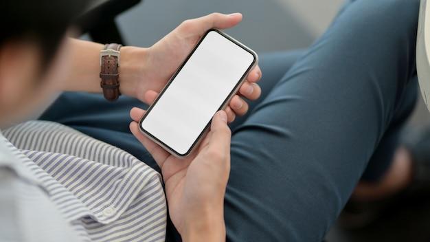 Крупным планом вид мужской держа смартфон во время отдыха на рабочем месте