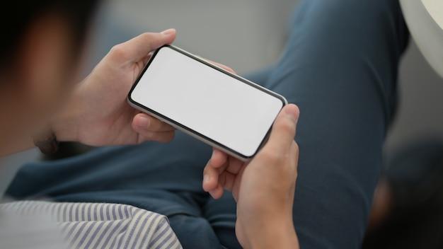 Крупным планом вид мужского предпринимателя, держа горизонтальный смартфон, лежа расслабленной