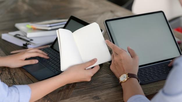 ノートを見ながらモックアップタブレットで入力する実業家のクローズアップ表示