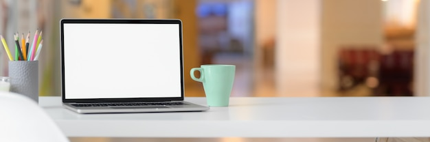空白の画面のラップトップ、マグカップ、文房具、コピースペースを持つシンプルなワークスペースのショットをトリミング