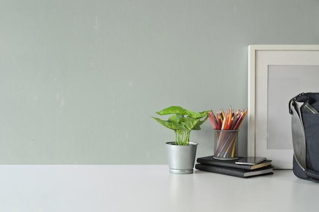 現代的なワークスペースの植物、モックアップのポスター、バッグ、コピースペース。
