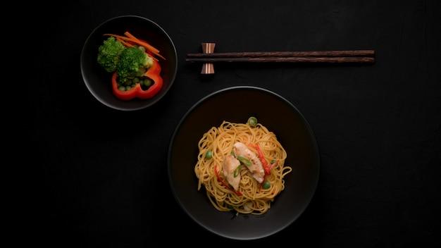 シェズワンヌードルまたはチャウメンの野菜、チキン、チリソース添えのトップビュー