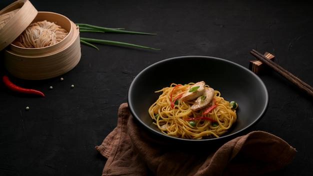シェズワンヌードルまたはチャウメンの野菜と鶏肉と黒いテーブルの食材のショットをトリミング