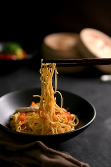 黒いテーブルに黒いボウルで中華麺のショットをトリミング