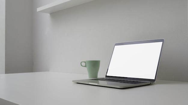 開いている空白の画面のラップトップ、マグカップ、コピースペースを持つ最小限のワークスペースのショットをトリミング