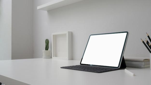 空白の画面のタブレット、装飾、文房具、コピースペースを持つ最小限のワークスペースのショットをトリミング