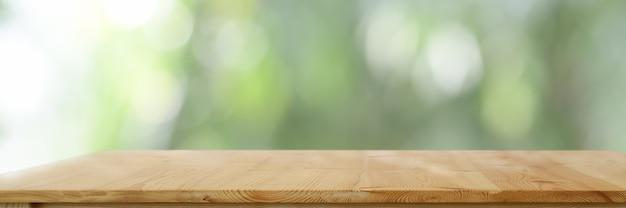 自然の背景をぼかした写真を空の木製テーブル