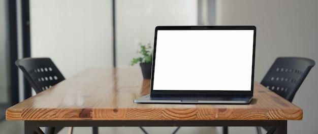 コワーキングスペースの木製の机の上のノートパソコンのクローズアップ表示