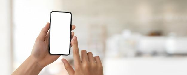 Человек трогательно на пустой экран смартфона в размытой стеклянной перегородке
