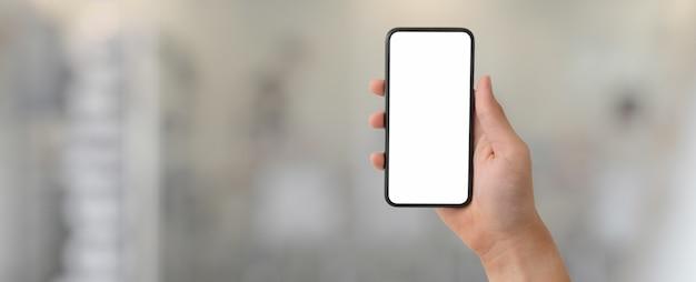 ぼやけたガラスパーティションオフィスで空白の画面のスマートフォンを示す男
