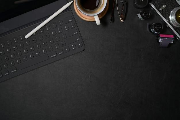 Вид сверху фотографа кожаный темный стол с креативными принадлежностями и копией пространства