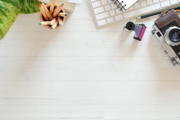 Офисный деревянный стол со старинной камерой, кофе, пленка, креативные принадлежности