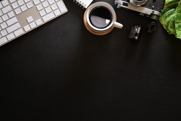 Офисный кожаный темный рабочий стол с круассаном, кофе, винтажной камерой, пленкой