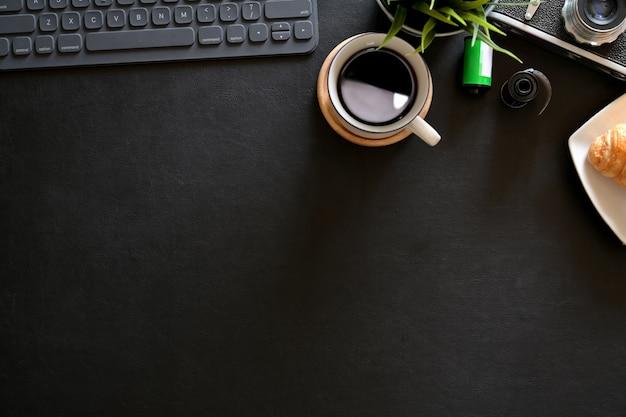 Офисный кожаный темный рабочий стол с круассаном, кофе, винтажной камерой, пленкой и копией пространства