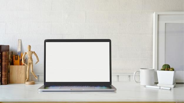 クリエイティブワークスペースモックアップポスターと机の上のノートパソコン