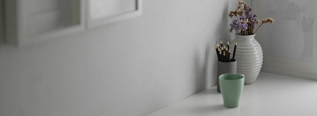 Обрезанный снимок белого современного дизайнера интерьера дома с кружкой, канцелярскими товарами и украшениями