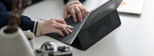 Обрезанный снимок фрилансера женского пола, работающего над современным рабочим столом