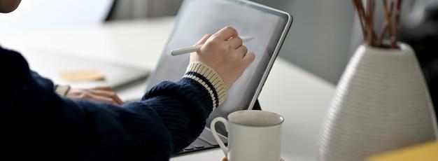 Обрезанный снимок женского фрилансера, опираясь на цифровой планшет со стилусом