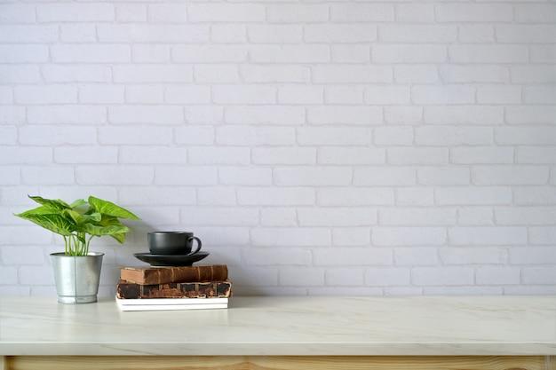 ワークスペースとコピースペース、本、大理石のトップテーブルの上のコーヒーマグ