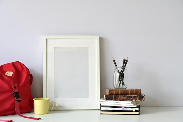 モックアップポスター、赤い袋、白いテーブルの上の供給とデスクトップ。学生ワークスペース