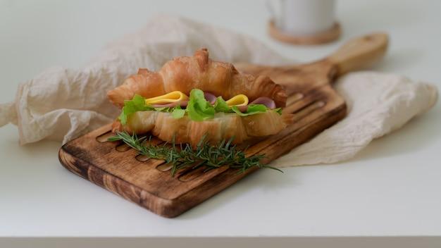 木製トレイのコーヒーとクロワッサンサンドイッチハムとチーズの朝食の食事のクローズアップ表示