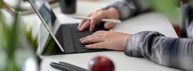 Взгляд со стороны женского графического дизайнера работая на цифровой таблетке на белой таблице
