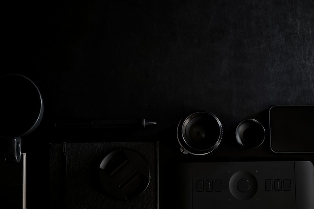 Рабочая область на черном кожаном столешнице креативного дизайнера или фотографа и копия пространства