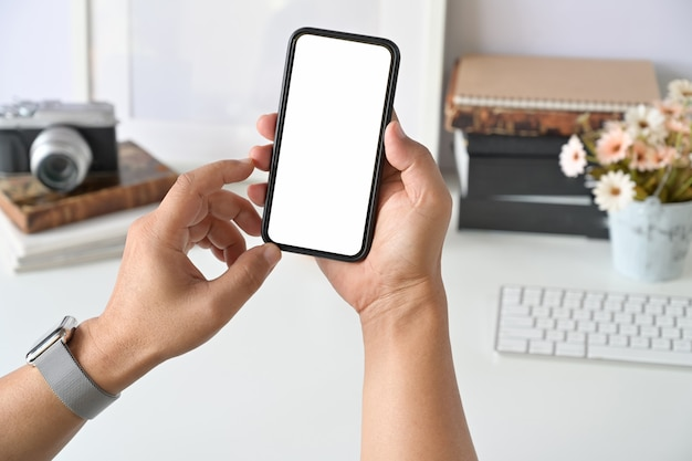 デスクワークで人間の手でモバイルのスマートフォン。
