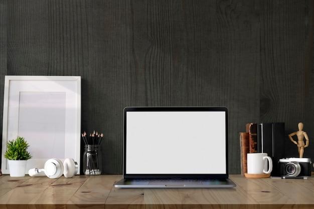 空白の画面のラップトップコンピューターとコピースペースを持つロフトワークスペースモックアップポスター。