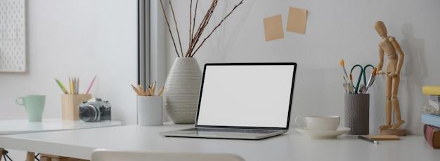 Обрезанный снимок дизайнерского рабочего пространства с ноутбуком, дизайнерскими принадлежностями, чашкой и украшением