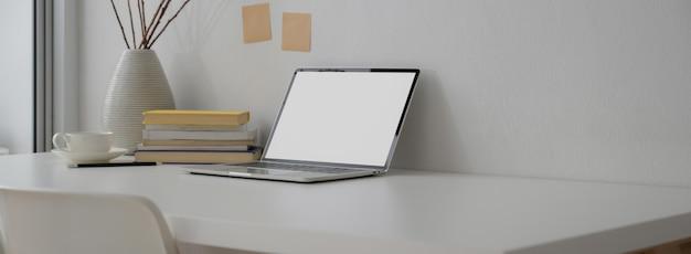 Обрезанный снимок портативного рабочего пространства с ноутбуком, книгами, отделкой и копией пространства