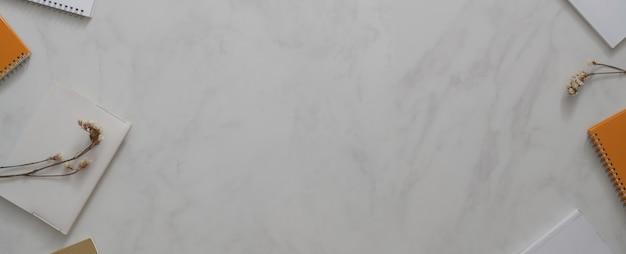 大理石の机の上に飾られたノートと花のあるモダンなワークスペース