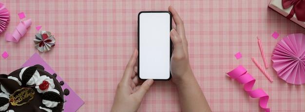 Женщина держит пустой экран смартфона на розовом фоне картины