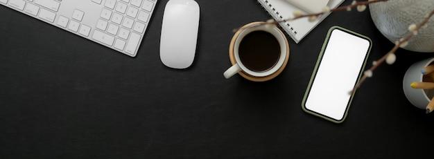 Черно-белое рабочее пространство со смартфоном, компьютерным устройством, кофейной чашкой, ноутбуком и копией пространства