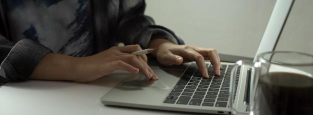 ポータブルワークスペースに座っているラップトップで電子メールを書く女性フリーランサー