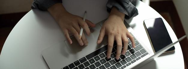 Женский фрилансер пишет электронную почту на ноутбуке, сидя на портативном рабочем пространстве