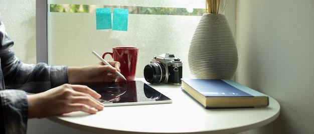 Женский фрилансер работает с цифровым планшетом на журнальный столик рядом с окном в гостиной