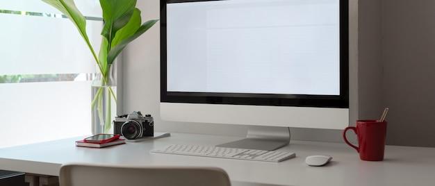 空白の画面のコンピューター、カメラ、マグカップ、事務用品、装飾が施されたスタイリッシュなオフィスデスク