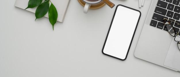 空白の画面のスマートフォン、ラップトップ、スケジュール帳、カップ、コピーの白い作業台
