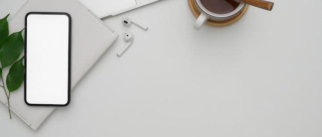 空白の画面のスマートフォン、ワイヤレスイヤホン、スケジュール帳、ホットココアカップのある白い作業台のスペースをコピーします。